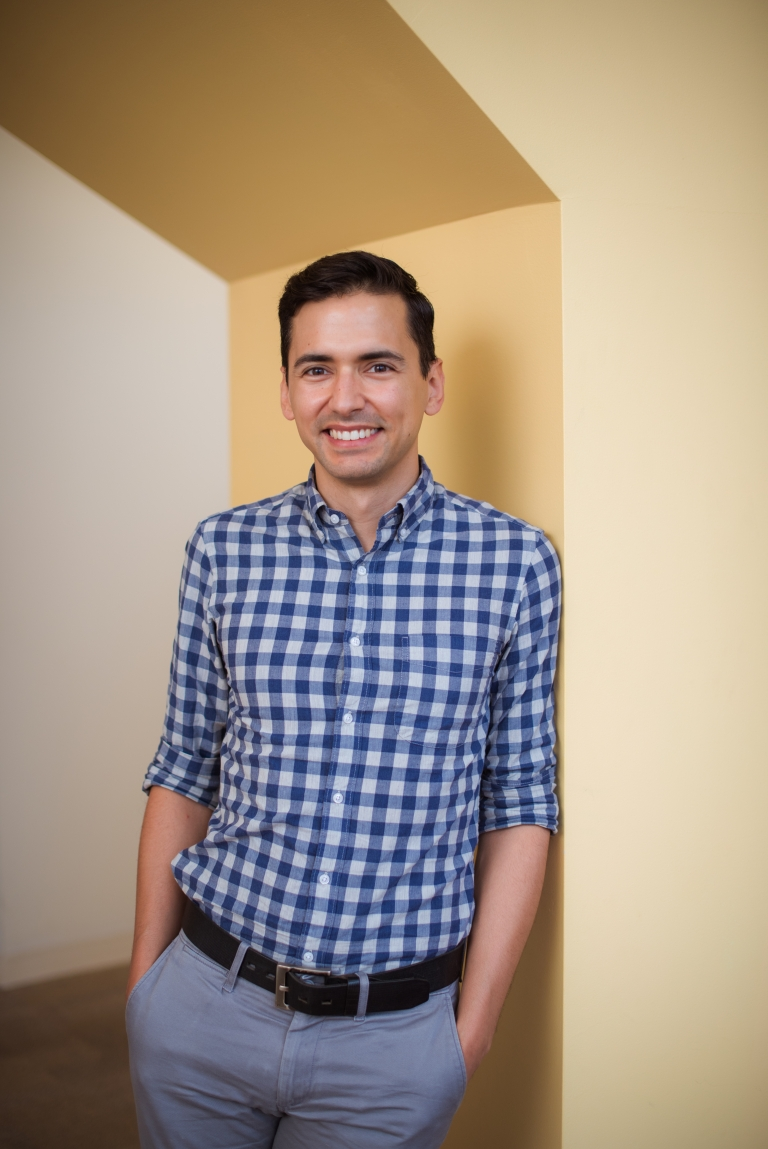 Sebastian Lourido stands smiling in an alcove.