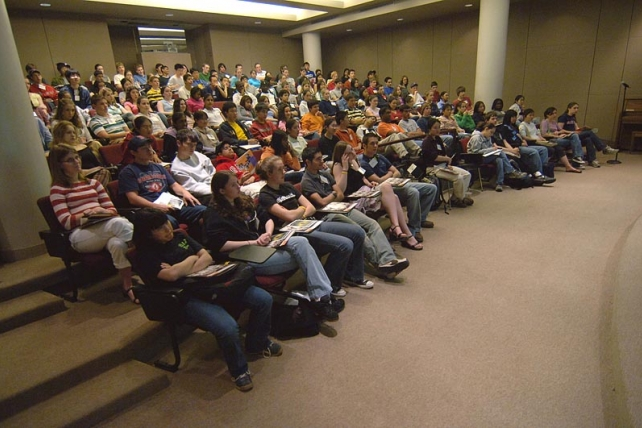Students sitting in a small auditorium for a lecture.