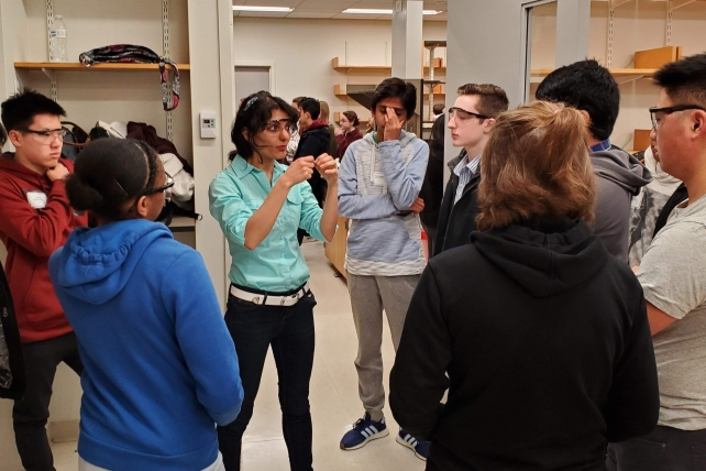 A person lectures to high school students in a lab room.